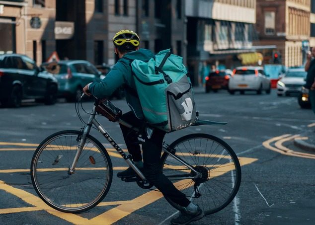 A Deliveroo rider cycling